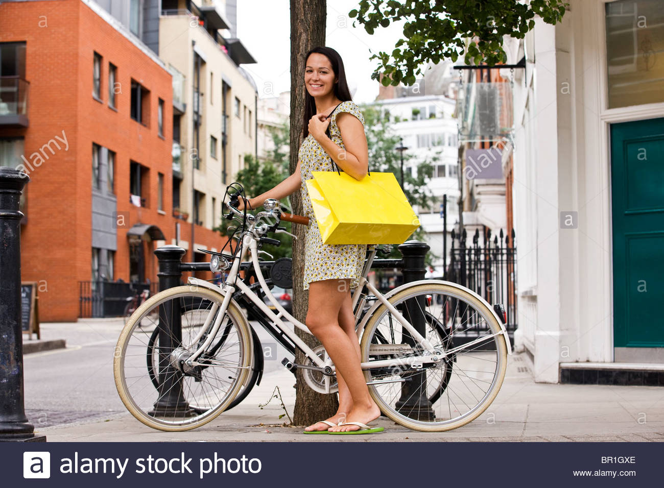 A young woman standing next to her bicycle, carrying a shopping bag - Stock Image