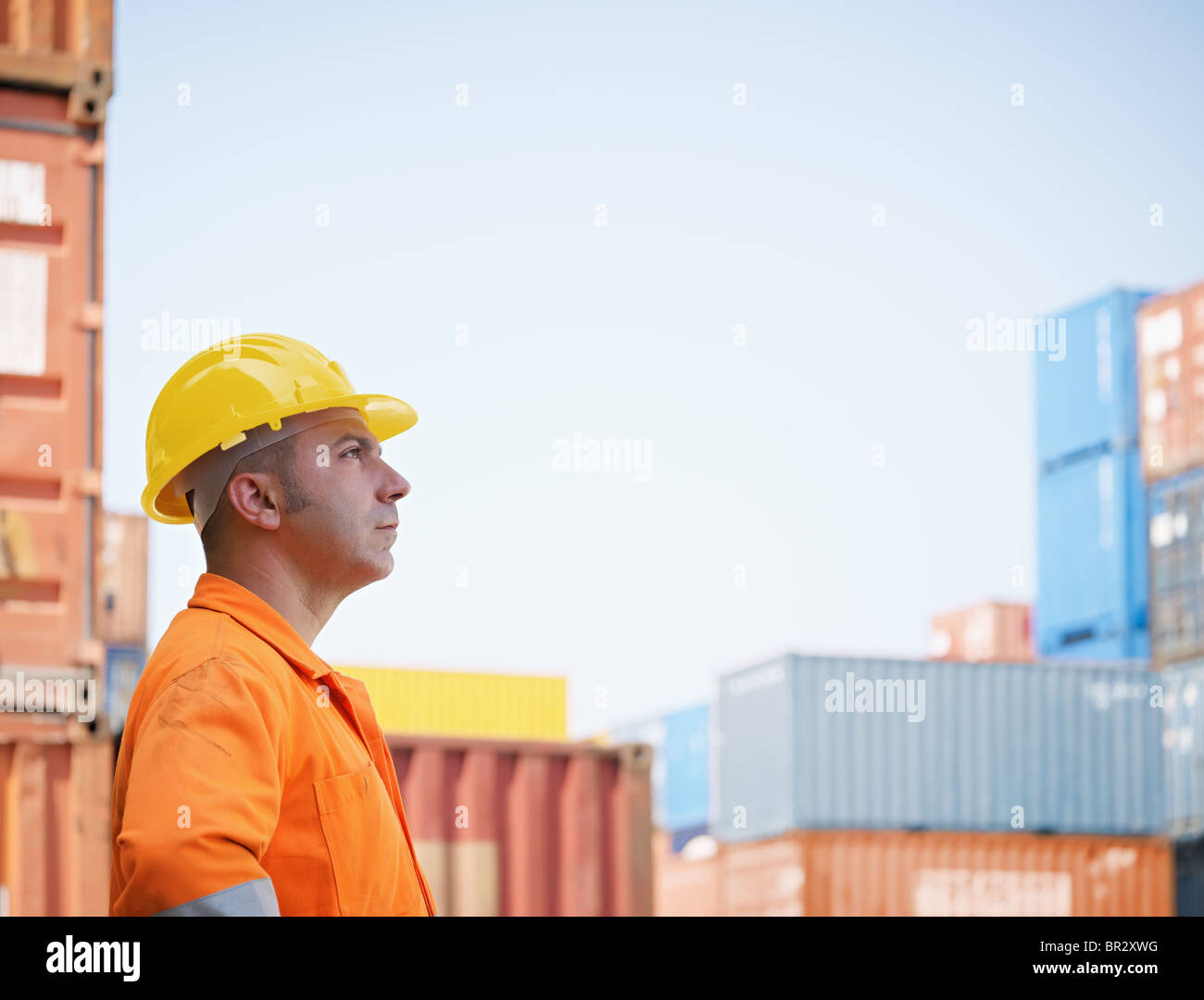portrait of mid adult worker looking at cargo containers. Horizontal shape, side view, copy space - Stock Image