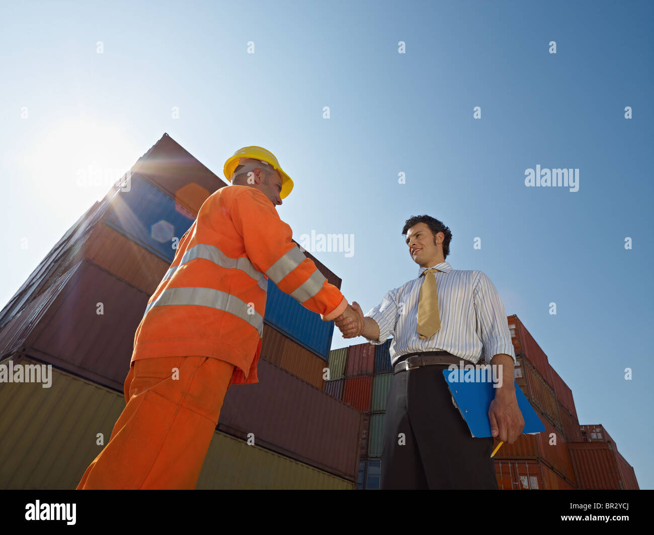 manual worker and businessman shaking hands near shipping containers - Stock Image