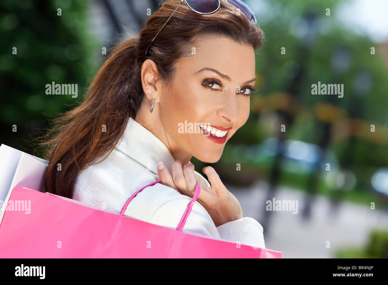 Beautiful, happy and fashionable woman with colorful pink and white shopping bags - Stock Image