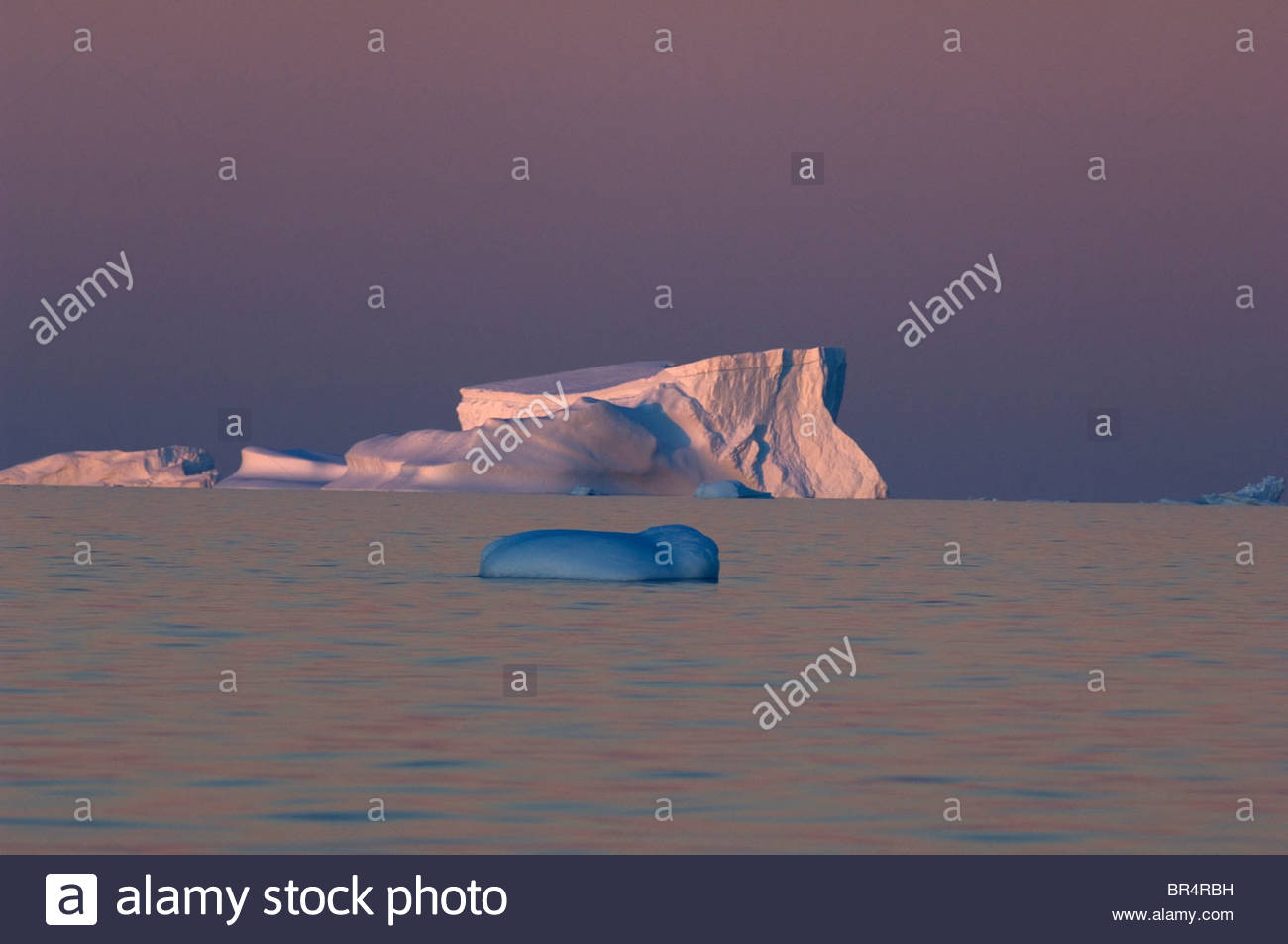 The pink sunset turns the normally blue water purple. The west coast of Antarctica's peninsula known as Graham - Stock Image