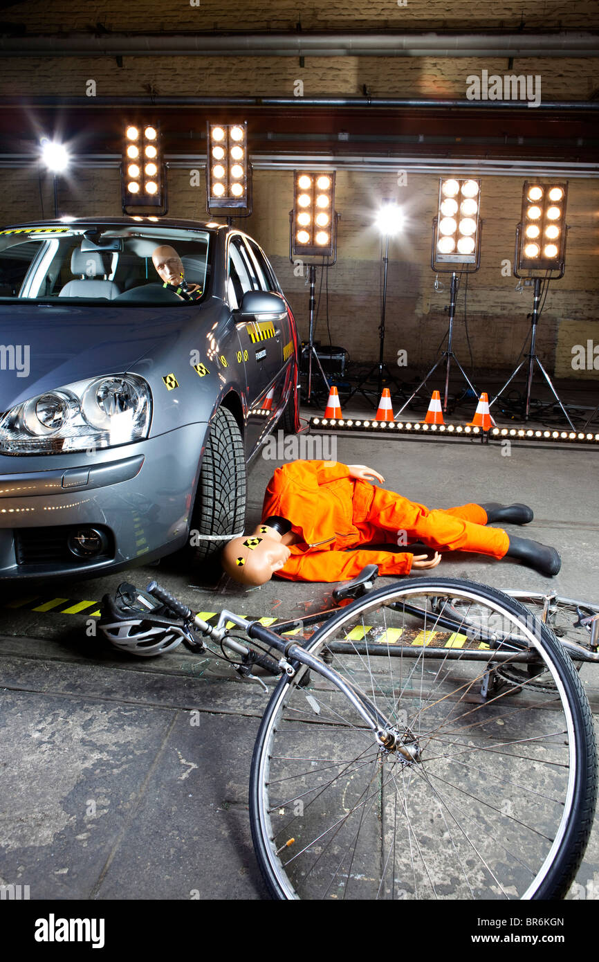 A crash test dummy on ground after bicycle crashed into car - Stock Image