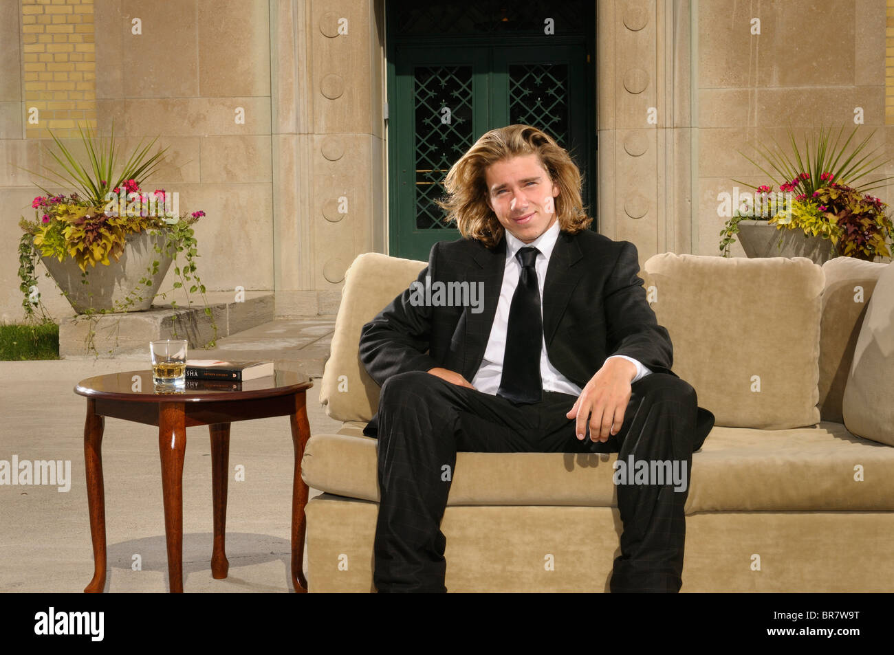 Wealthy young man with long blond hair in suit sitting on a couch on an outdoor terrace at a mansion - Stock Image