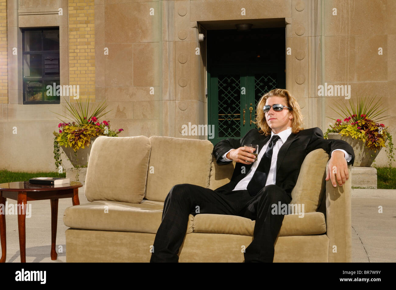Wealthy young man with long blond hair in suit sitting on a couch with a drink on an outdoor terrace at a mansion - Stock Image