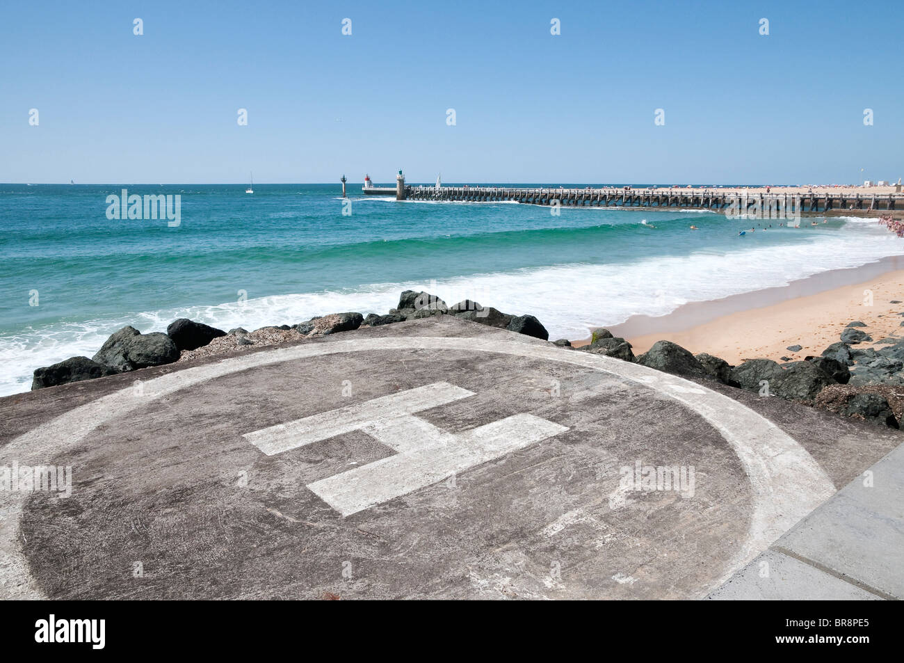 Landing area on the beach with sea and a jetty in the background during a beautiful day Stock Photo