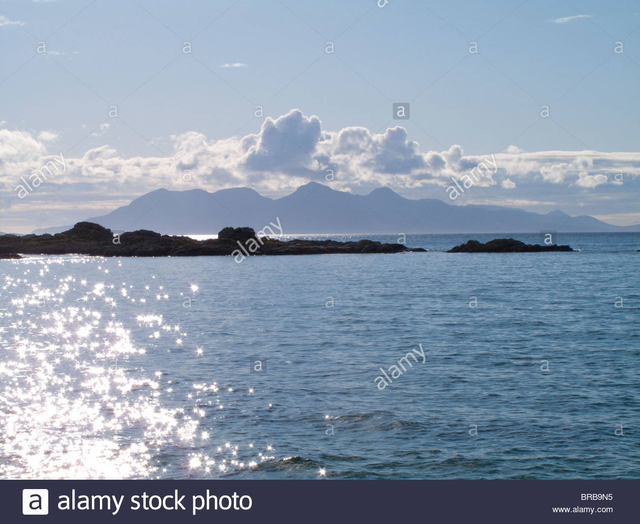 Rocks in tranquil ocean with mountain in background - Stock Image