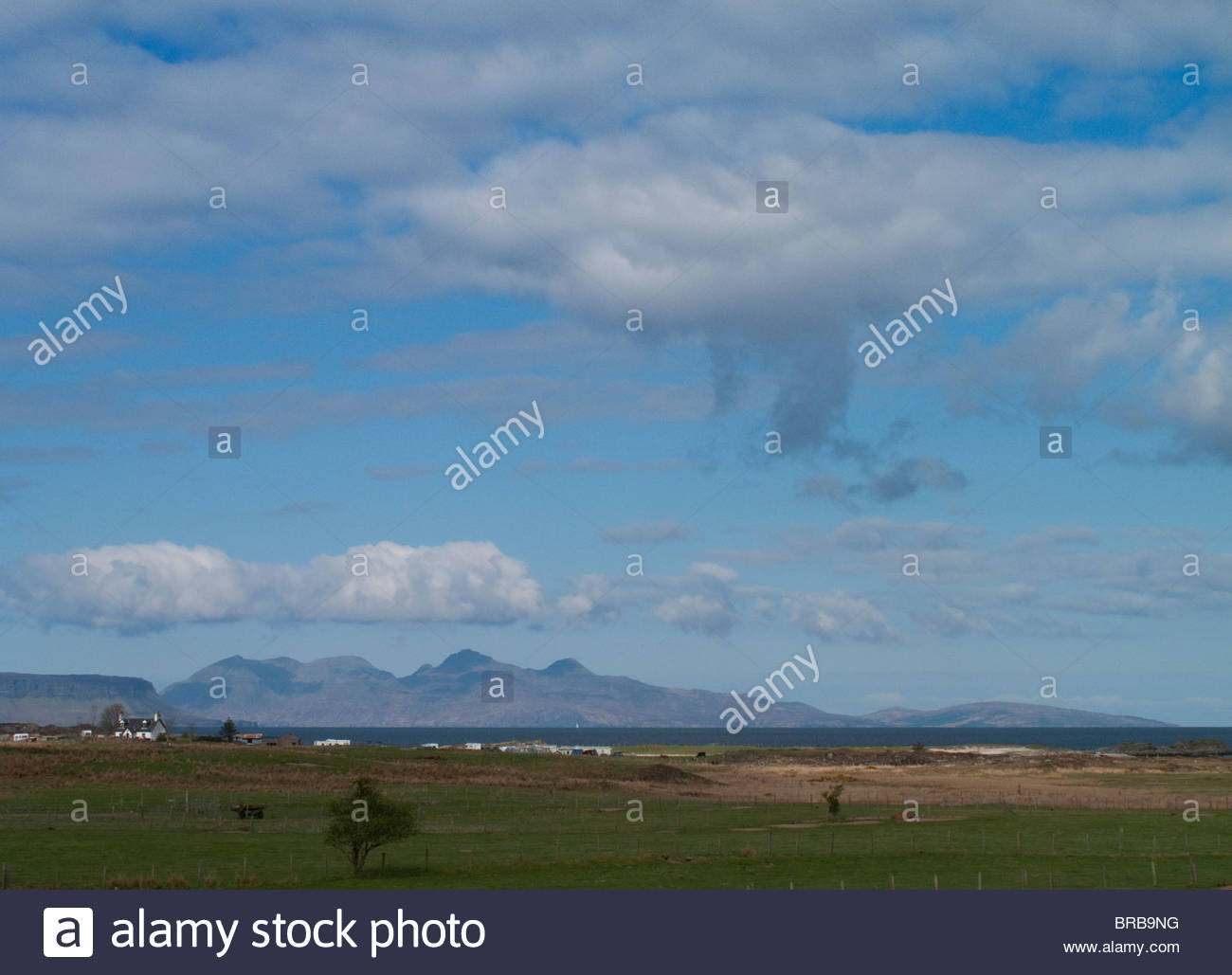 Tranquil farmland and houses under blue sky - Stock Image
