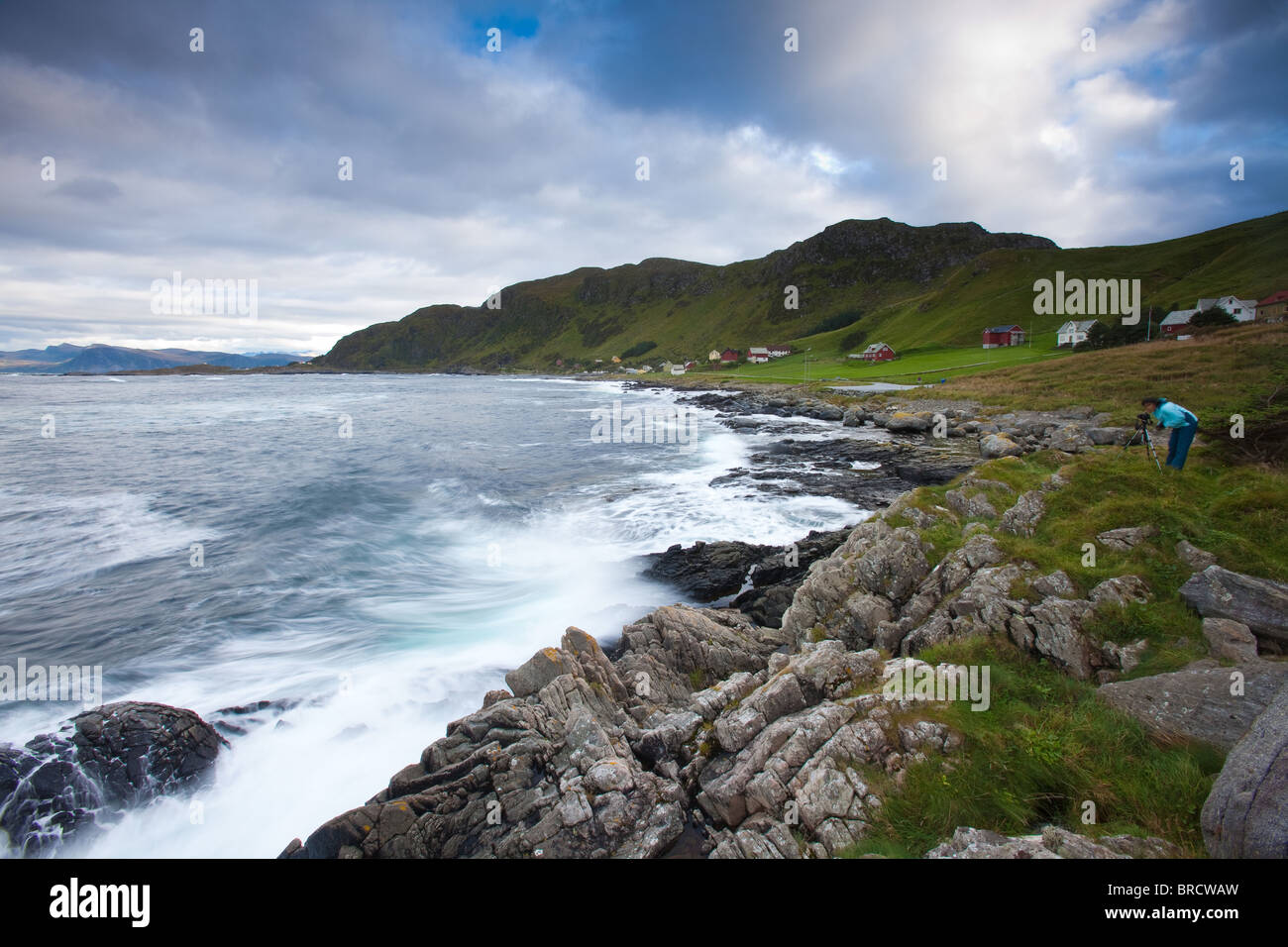 Photographer at work near the small community Goksøyr on the island Runde on the west coast of Norway. - Stock Image