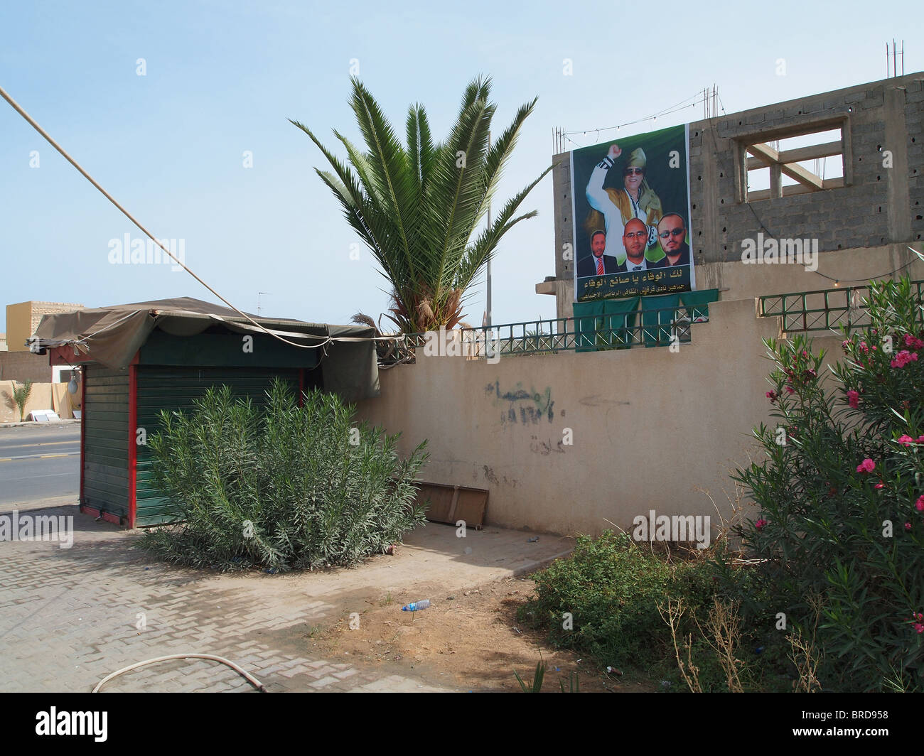 Qaddafi poster and traffic in Tripoli - Stock Image