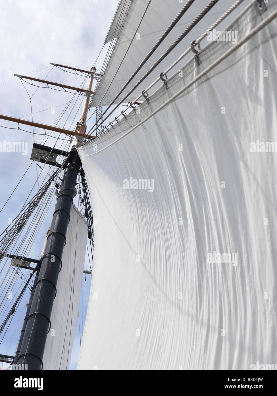 Tall ship triangular jib sails and a mast over blue sky background - Stock Image