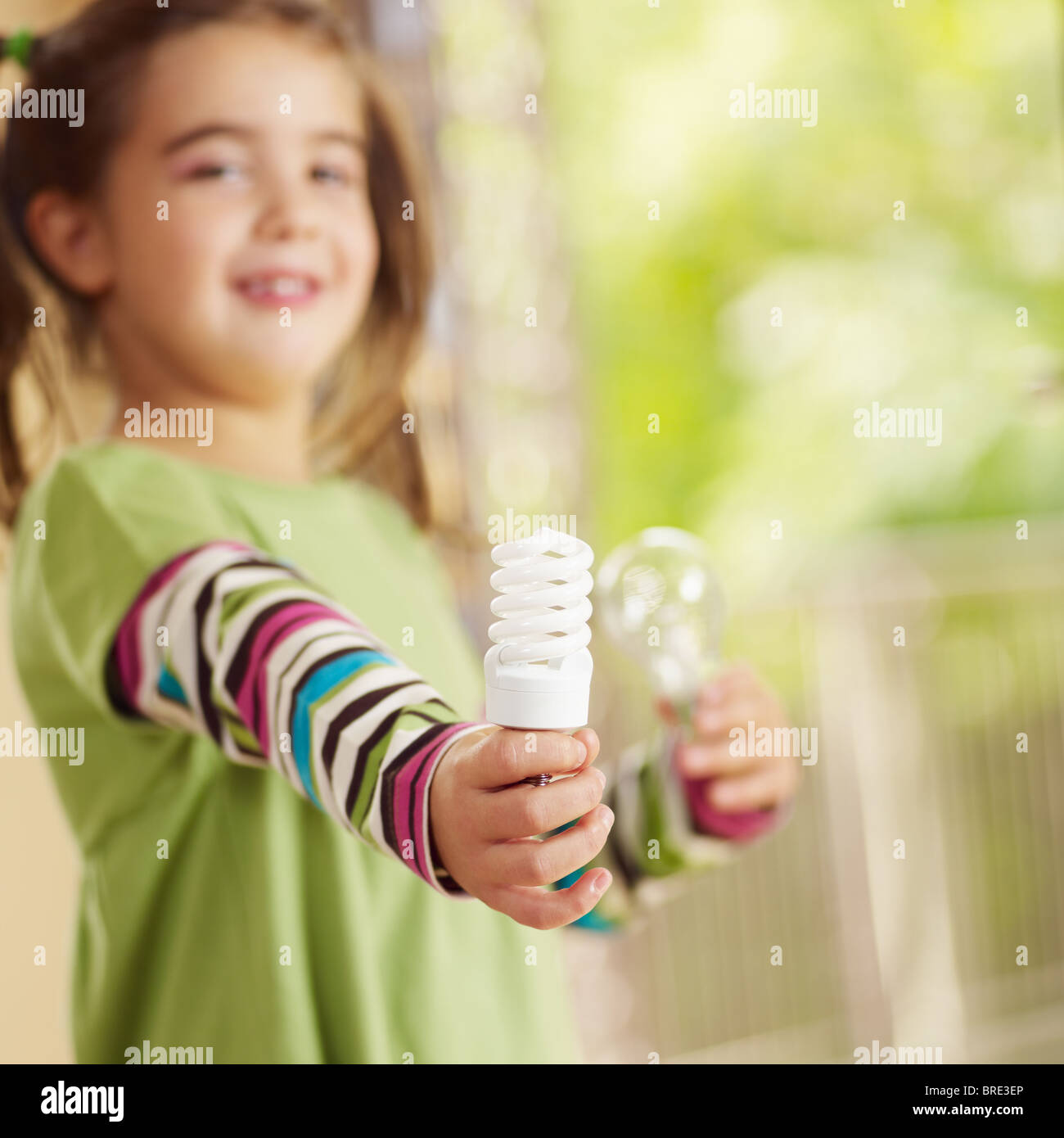 Girl holding light bulb and smiling. Selective focus, copy space - Stock Image