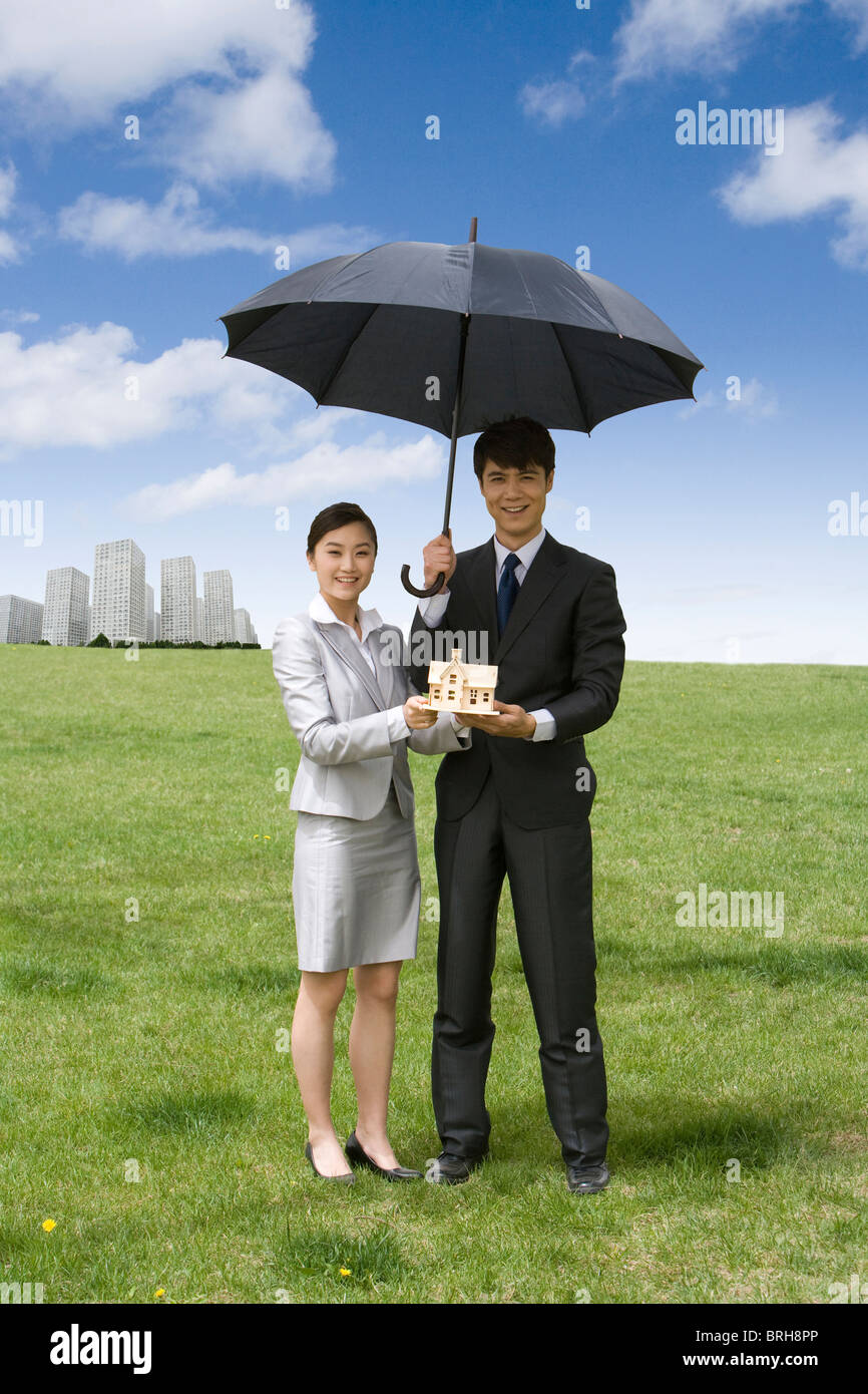 Woman and man holding a model house with an umbrella - Stock Image