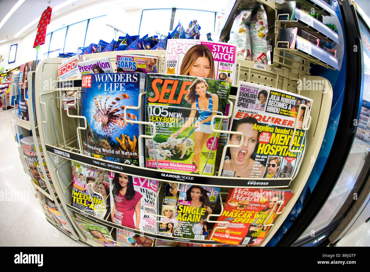 tabloid sensational news stories magazine rack in a store, United States - Stock Image