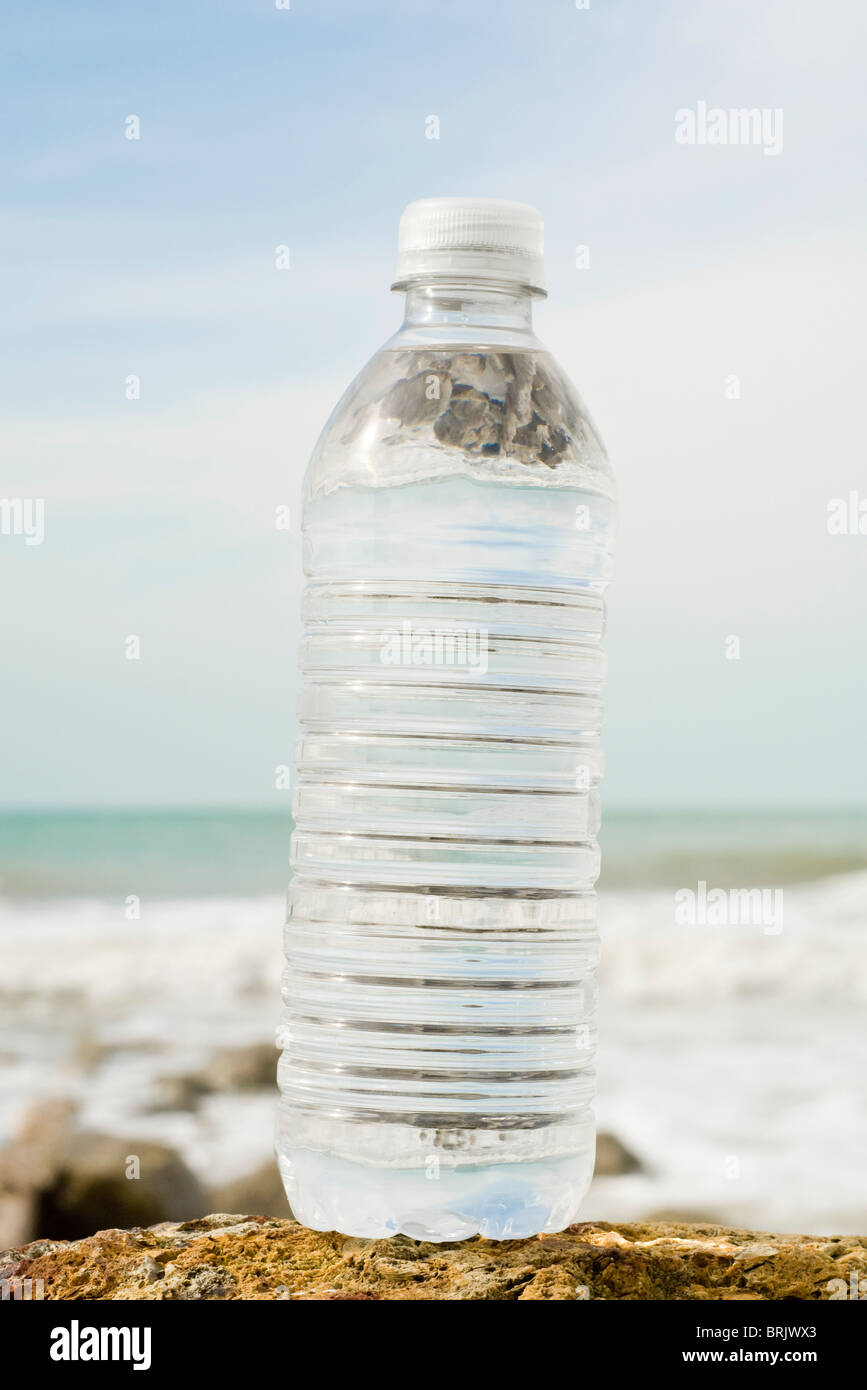 Bottle of water on shore - Stock Image
