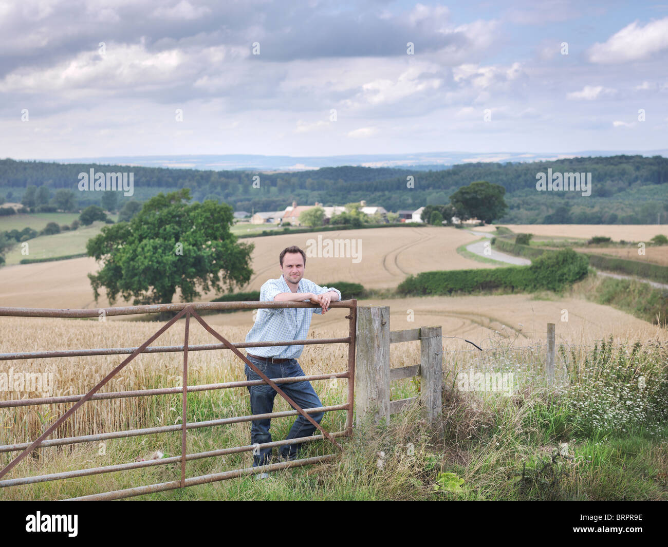 Farmer with crops and farm - Stock Image