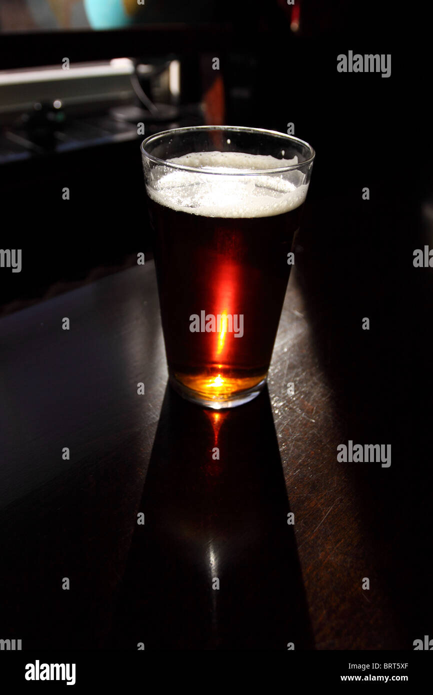 Pint of beer glass bitter beer in English pub - Stock Image