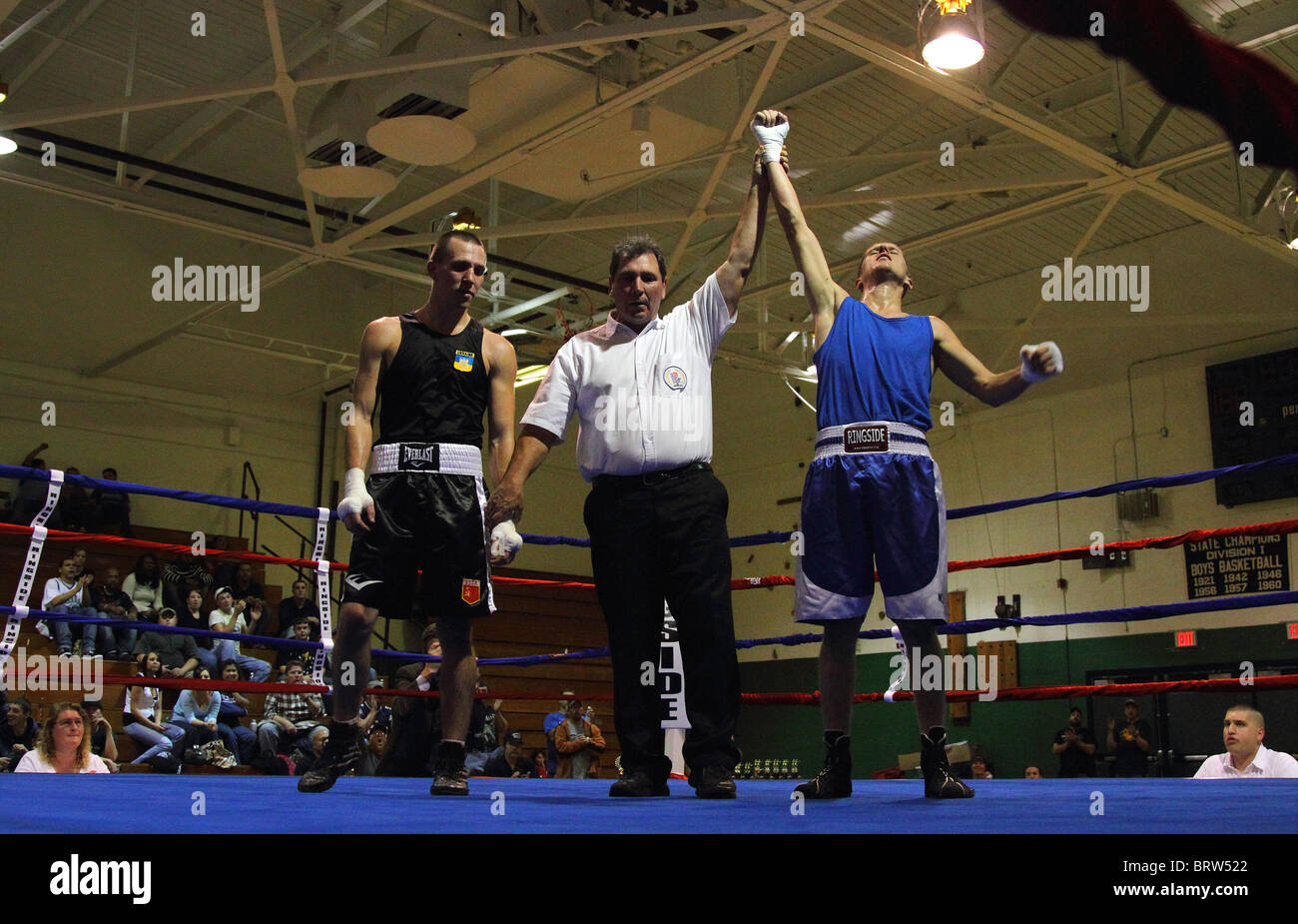Boxing referee holds up winning boxer's arm in the ring after a boxing match - Stock Image
