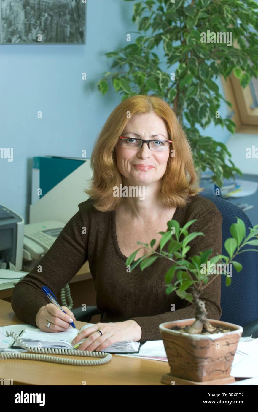 portrait of mature secretary at desk stock photo: 31935895 - alamy