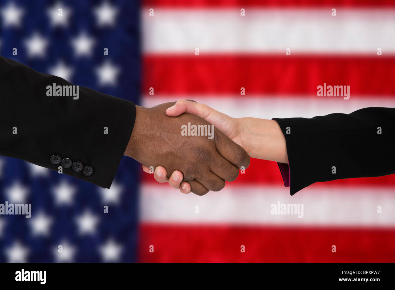 Close-up of people shaking hands against American flag - Stock Image