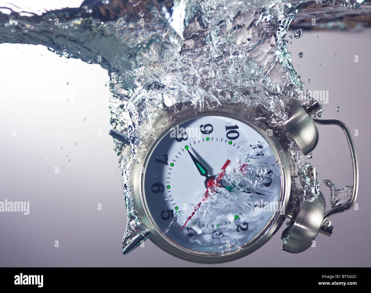 Alarm clock sinks underwater - Stock Image