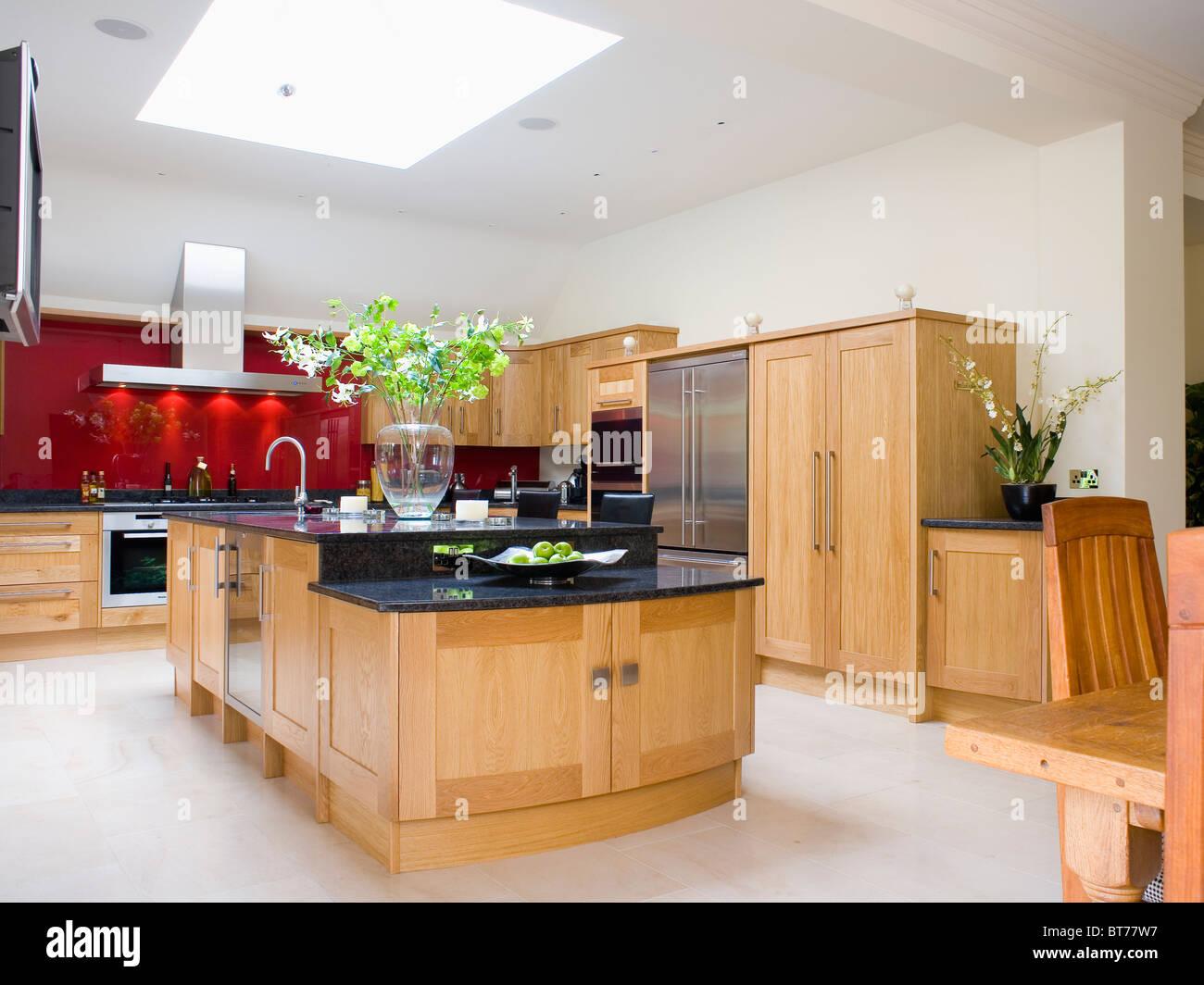 Pale Wood Island Unit With Black Granite Worktop In Large Modern Kitchen Extension Limestone Flooring