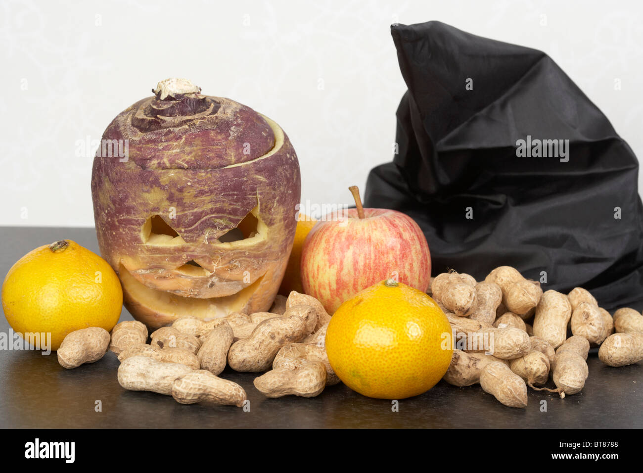 the spoils from trick or treating with halloween turnip jack-o-lantern. Traditionally in Ireland turnips or swedes - Stock Image