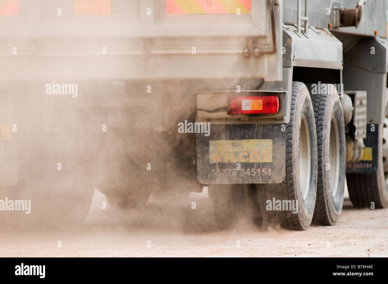 lorry kicking up dust dusty road roads earth mover truck trucks fine powdery fine - Stock Image