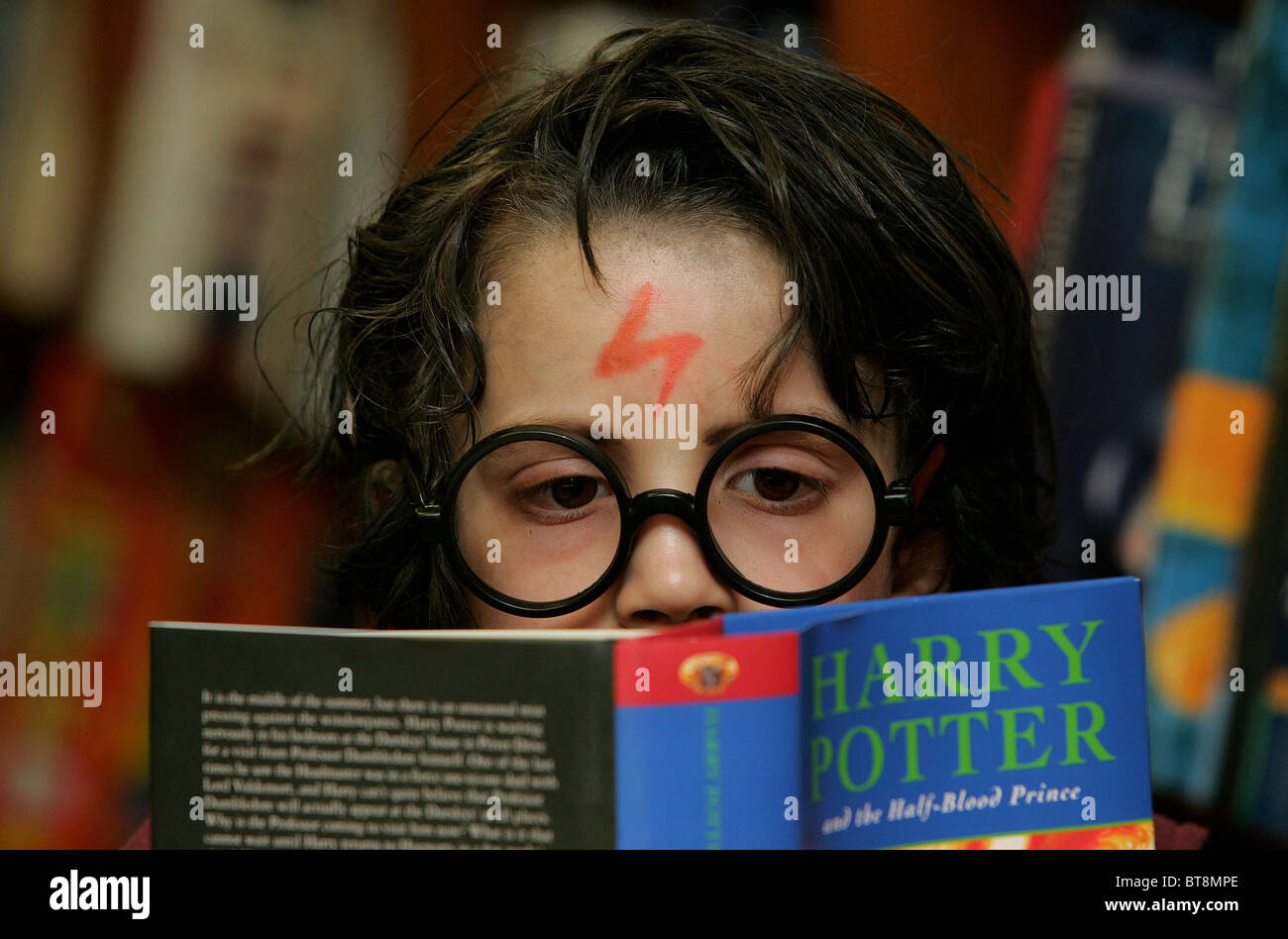 A young boy reading 'Harry Potter and the half blood prince' dressed up as Harry Potter Picture by James - Stock Image