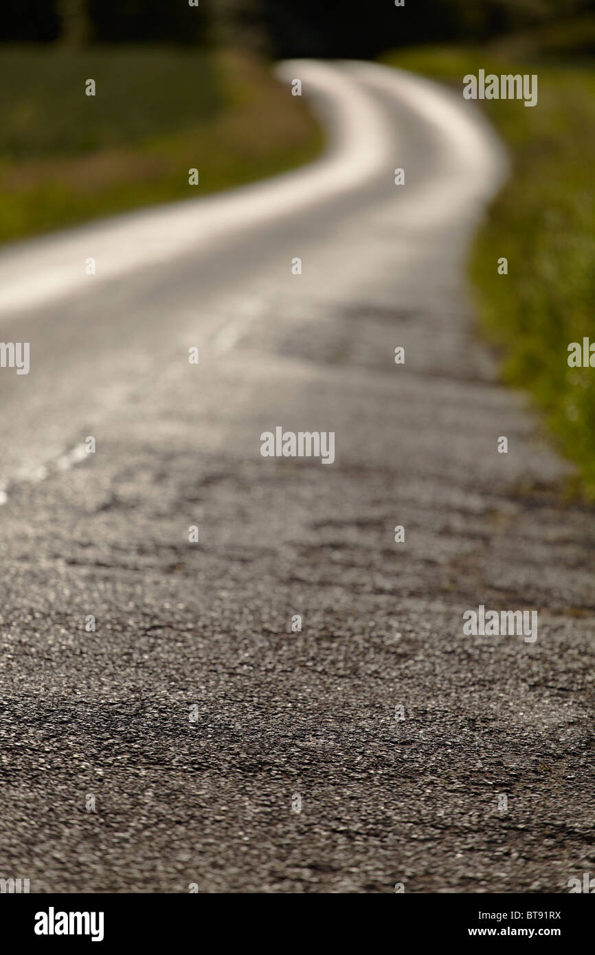 Winding country lane on a summer's evening (shallow depth of field). - Stock Image