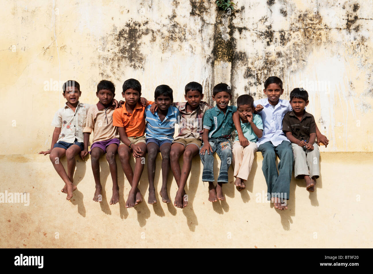 Rural South Indian village boys sitting on school wall in bright sunlight. Andhra Pradesh, India - Stock Image