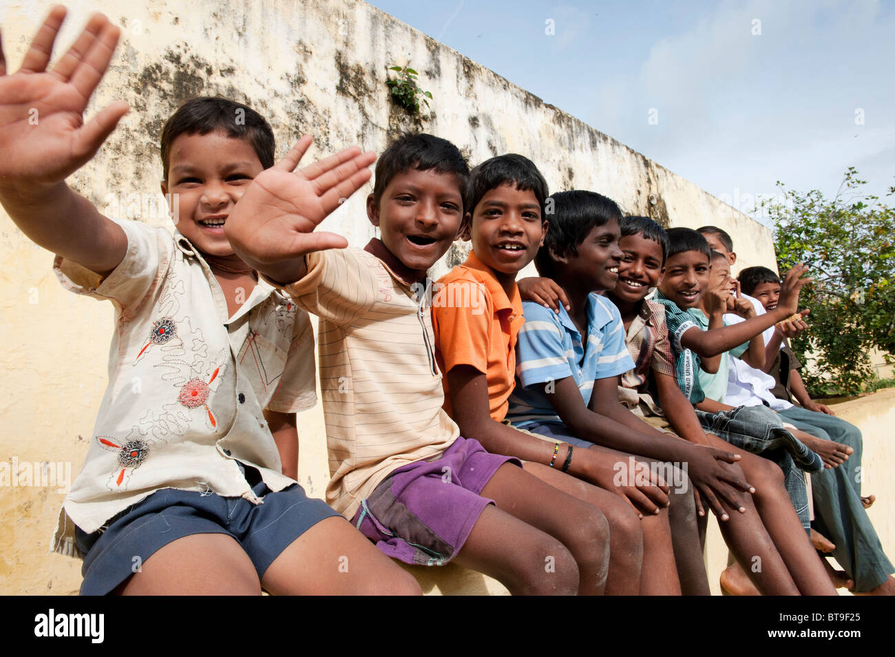 Rural Indian village boys sitting on a school wall waving in bright sunlight. Andhra Pradesh, India - Stock Image