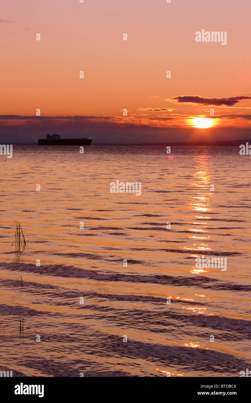 View of cargo ship sailing up Knik Arm towards the Port of Anchorage at sunset, Southcentral, Alaska, Summer - Stock Image