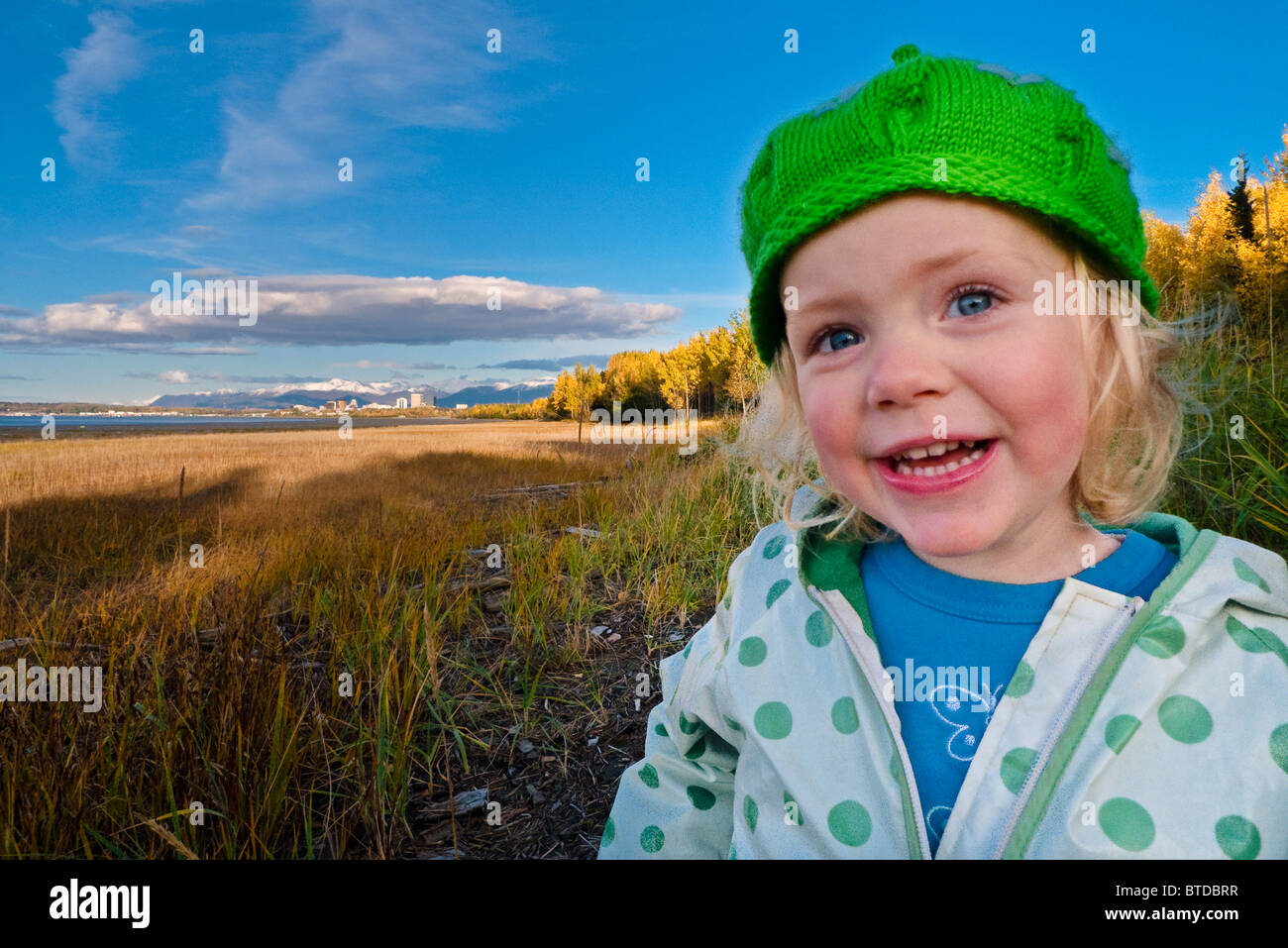 Female toddler in a green hat stands on the mud flats next to the Coastal Trail with Anchorage in the distance, - Stock Image