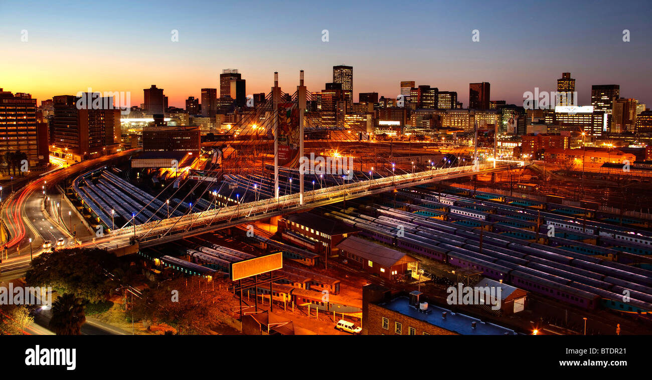 Sunrise over the city of Johannesburg with Nelson Mandela Bridge and the rail yards of Park Station. - Stock Image