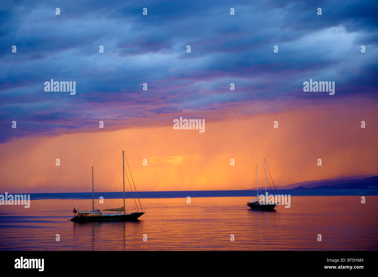 Sailing boats at sunset off Mykonos, Cyclades Isalnd, Greece - Stock Image