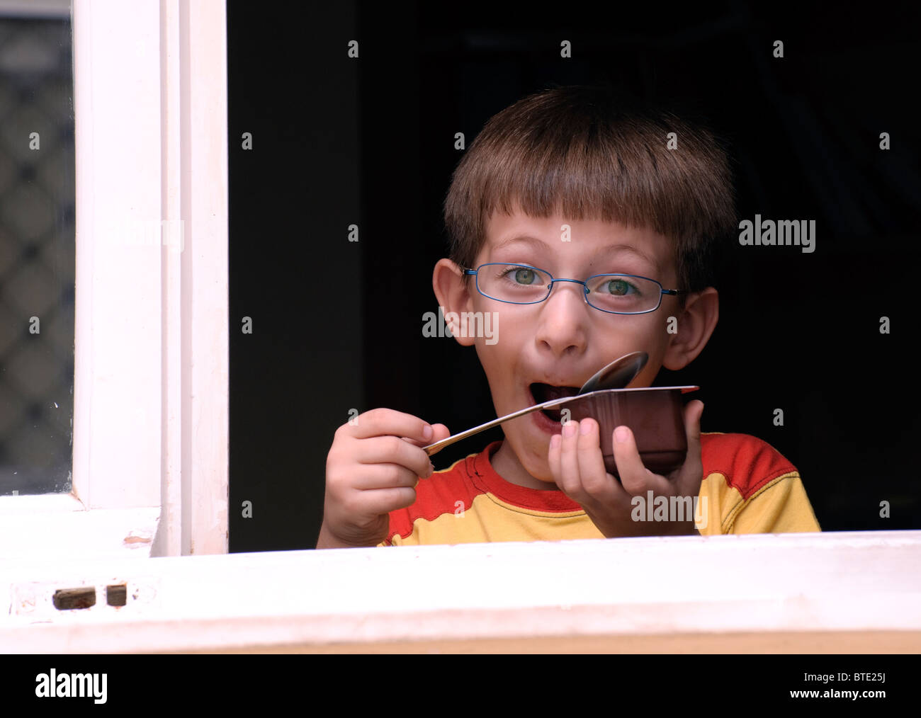 young-greek-boy-making-a-funny-face-as-he-is-eating-some-chocolate-BTE25J.jpg