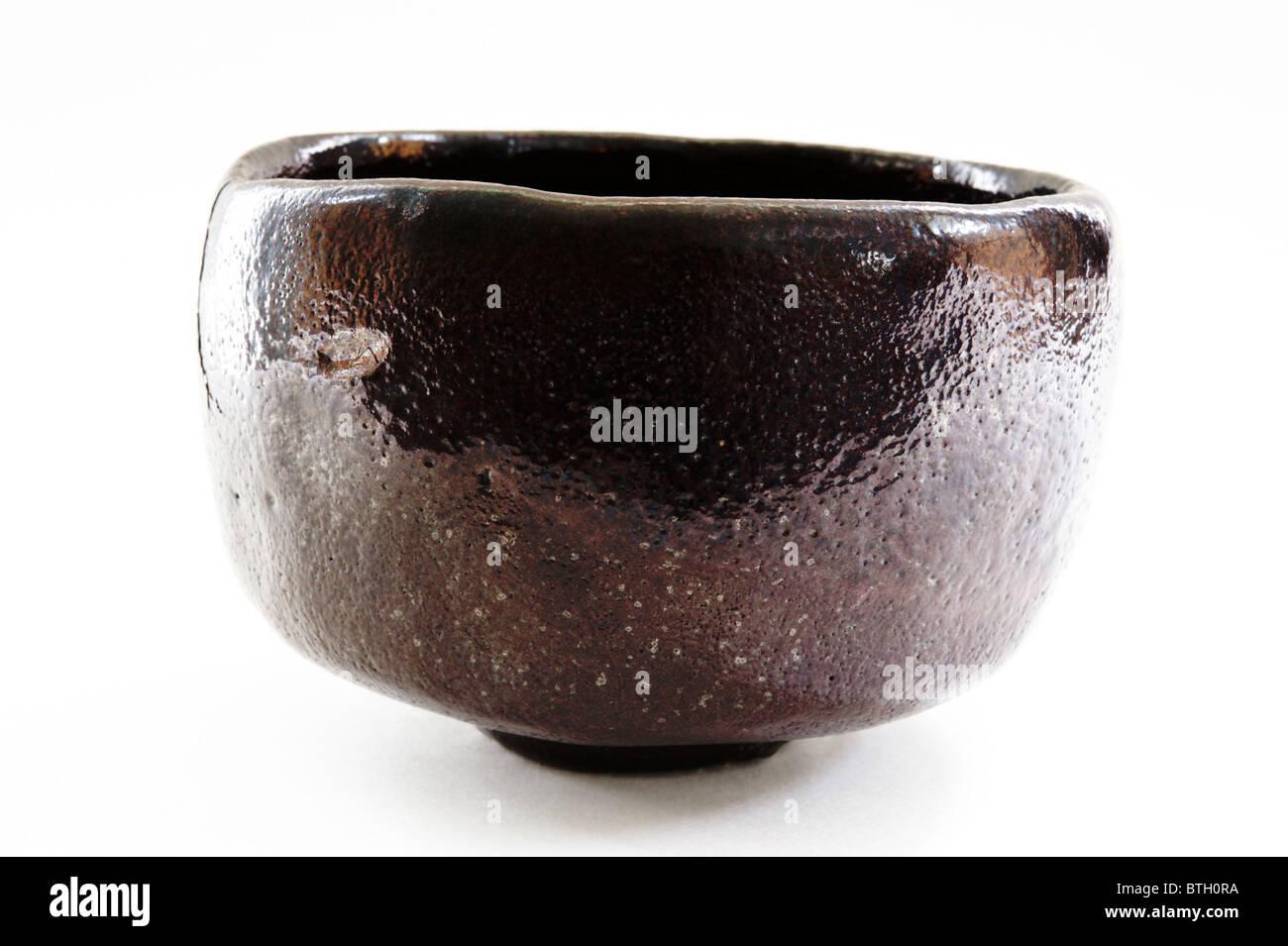 japanese raku style tea bowl with dark brown to black glaze on ajapanese raku style tea bowl with dark brown to black glaze on a white background