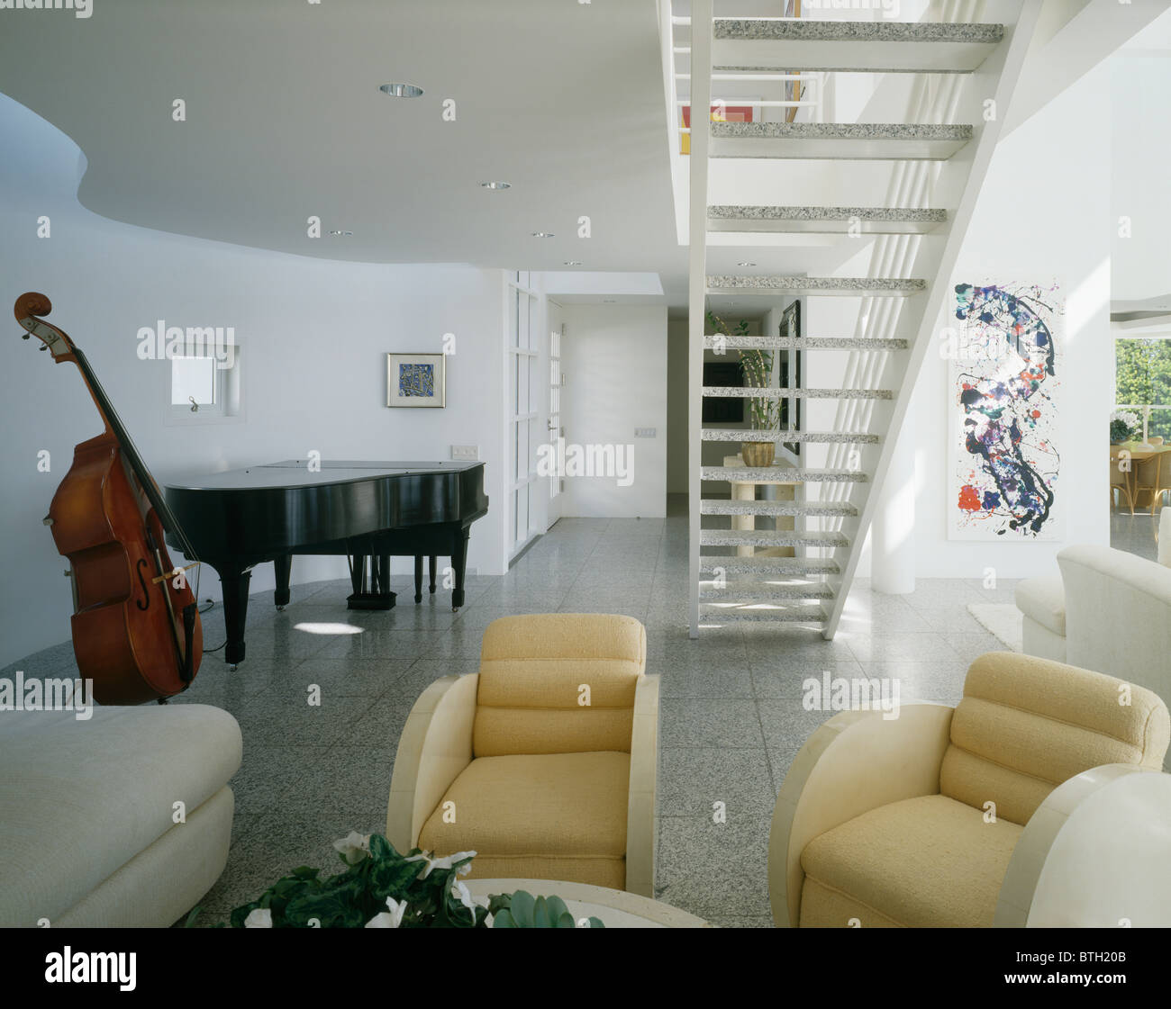 Grand Piano And Bass Viol In Large Modern Living Room With Cream Art Deco  Style Armchairs Below Open Staircase
