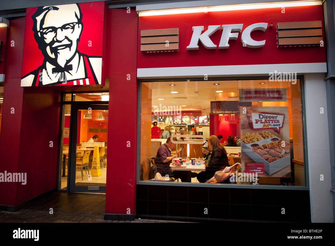 Exterior, night, people eating in a branch of KFC, kentucky fried chicken, fast food restaurant, UK Stock Photo