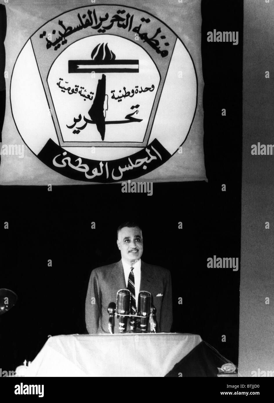 President of the United Arab Republic Gamal Abdel Nasser, standing under the symbol of the PLO (Palestine Liberation - Stock Image