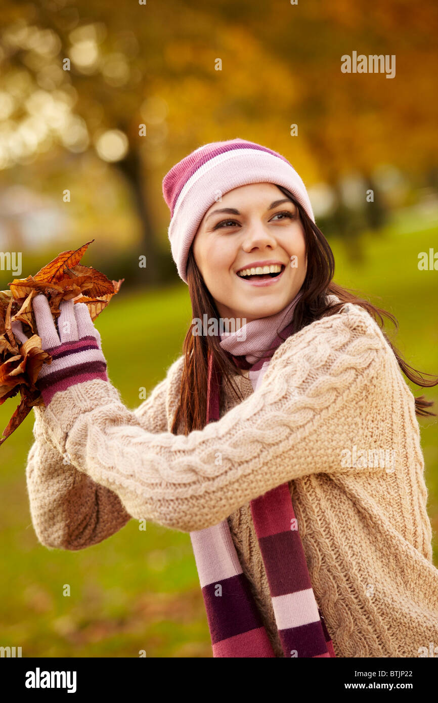 Brunette girl collecting Autumn leaves - Stock Image