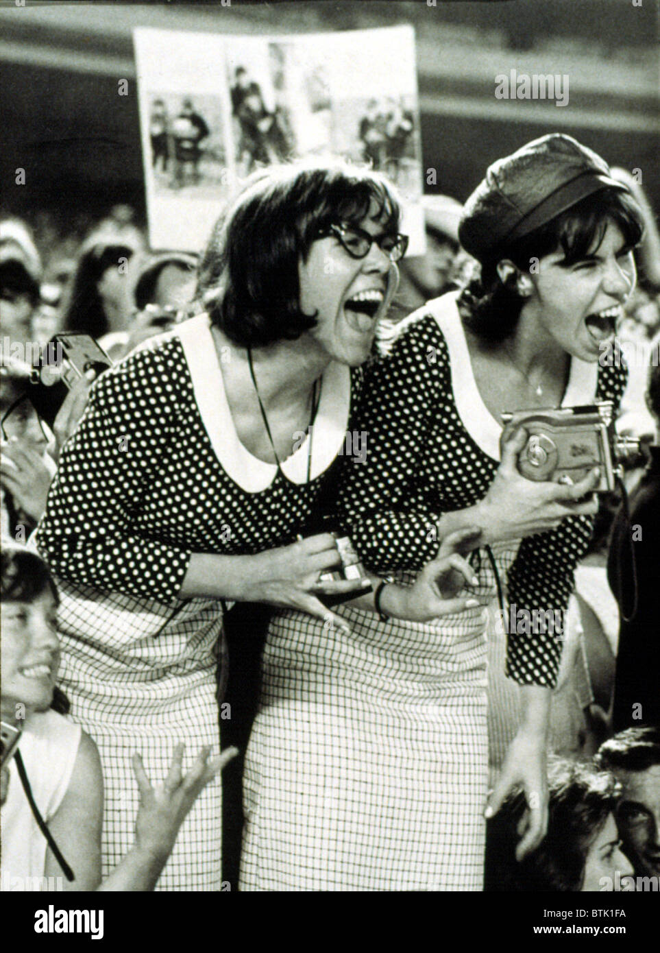 "BEATLES FANS scream at a concert at Shea Stadium, NY, 8/15/65, displaying what is called, ""Beatlemania."" Stock Photo"