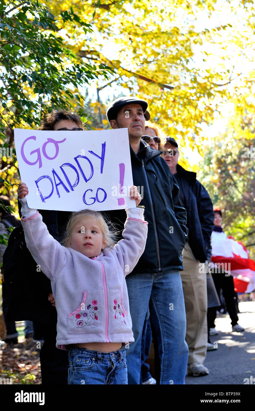 New York - Nov 7, 2011:  Cute little girl in crowd holds sign saying Go Daddy Go watching the 2010 New York City Stock Photo