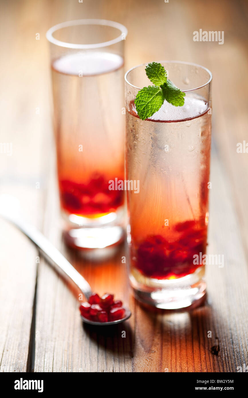 two cold pomegranate drinks or cocktails - Stock Image