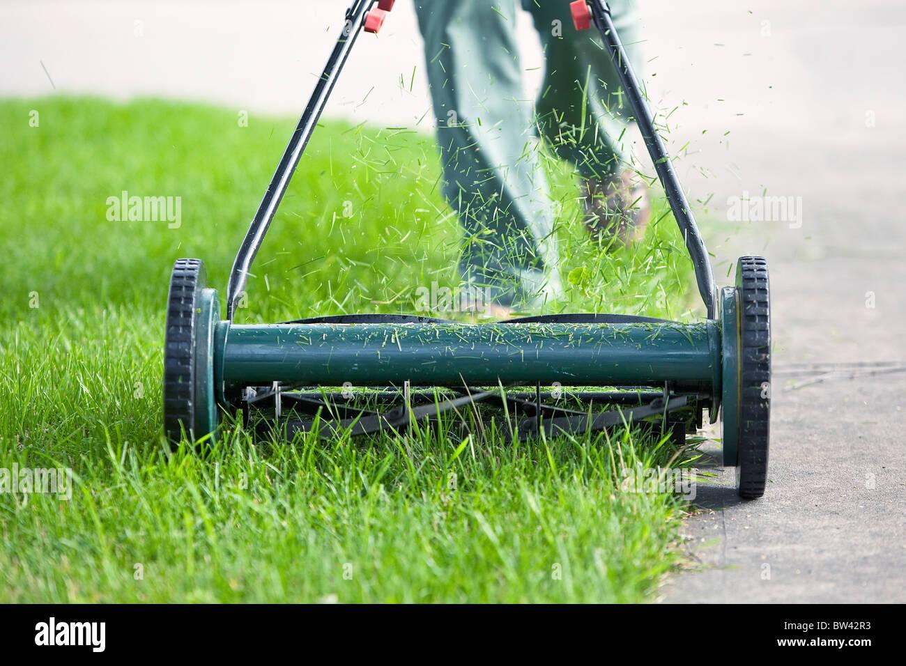 Woman cutting grass with an environmentally friendly push lawn mower, Winnipeg, Manitoba, Canada - Stock Image