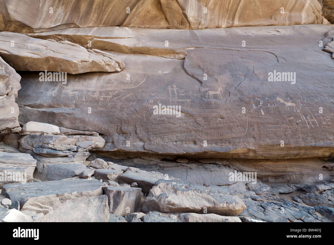 Petroglyph of large boat and various animals overlaid by modern painted graffiti, Wadi el-Barramiya, Eastern Desert, - Stock Image