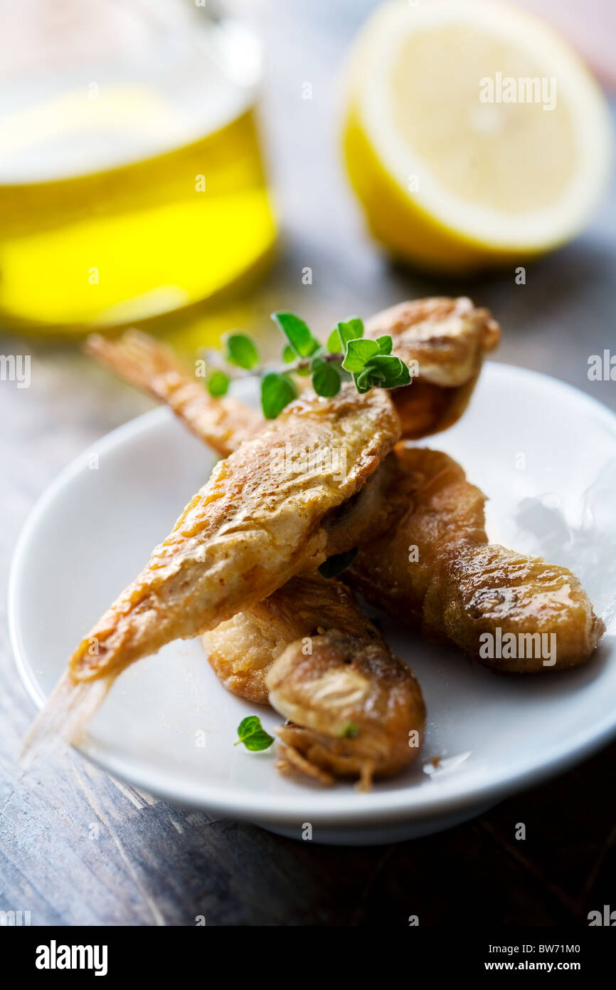 type of small red mullet, fried in olive oil, flour and salt, spinkled with oregano and lemon, a typical mediterranean - Stock Image