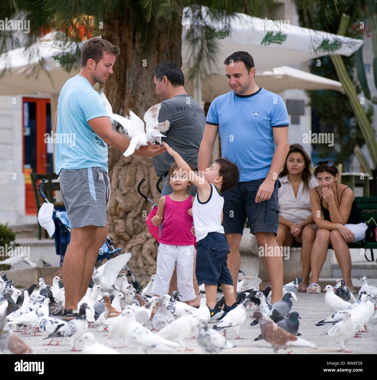 adults-showing-children-how-to-feed-the-pigeons-on-miaoulis-square-BW8F28.jpg