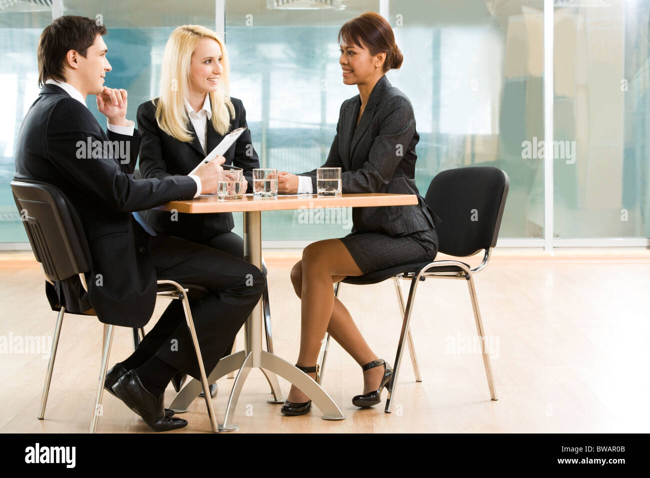 Three business partners discussing important affairs at working meeting - Stock Image