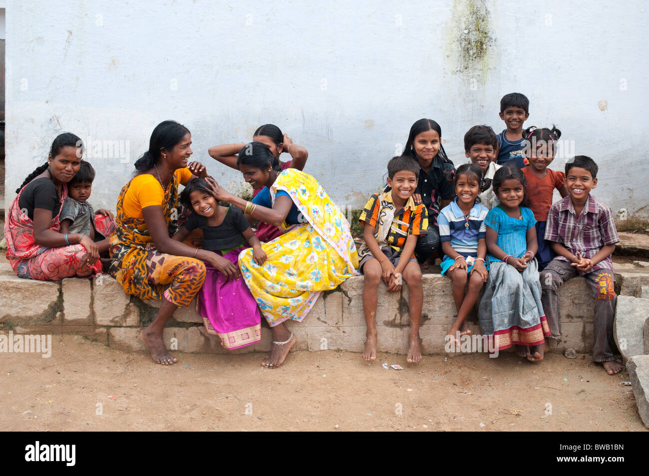 Indian mothers nitpicking young girls head in a rural indian village community. Andhra Pradesh, India - Stock Image
